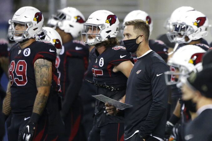 Arizona Cardinals head coach Kliff Kingsbury wears a mask as he stands with his team before an NFL football game against the Seattle Seahawks, Thursday, Nov. 19, 2020, in Seattle. (AP Photo/Lindsey Wasson)