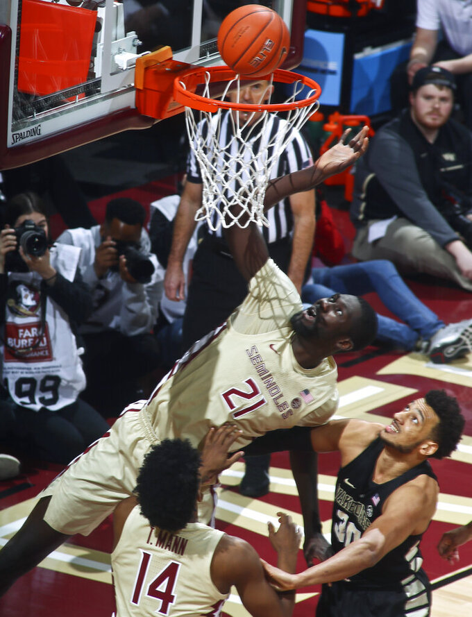 Florida State center Christ Koumadje (21) dunks as Florida State guard Terance Mann (14) and Wake Forest center Olivier Sarr (30) watch during the first half of an NCAA college basketball game in Tallahassee, Fla., Wednesday, Feb. 13, 2019. (AP Photo/Phil Sears)