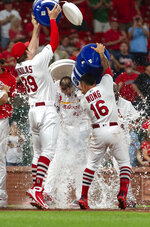 St. Louis Cardinals' Kolten Wong, right, and Miles Mikolas, left, dump water onto Paul Goldschmidt after he hit the game-winning home run during the 11th inning of a baseball game against the Miami Marlins, Wednesday, June 19, 2019, in St. Louis. The Cardinals won 2-1. (AP Photo/L.G. Patterson)