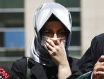 Hatice Cengiz, the fiancee of slain Saudi journalist Jamal Kashoggi, reacts as she talks to members of the media outside a court in Istanbul, Friday, July 3, 2020, where the trial in absentia of two former aides of Saudi Crown Prince Mohammed bin Salman and 18 other Saudi nationals over the 2018 killing of the Washington Post columnist had began. Turkish prosecutors have indicted the 20 Saudi nationals over Khashoggi's grisly killing at the Saudi Consulate in Istanbul that cast a cloud of suspicion over Prince Mohammed and are seeking life prison terms for defendants who have all left Turkey. Saudi Arabia rejected Turkish demands for the suspects' extradition and put them on trial in Riyadh.(AP Photo/Emrah Gurel)