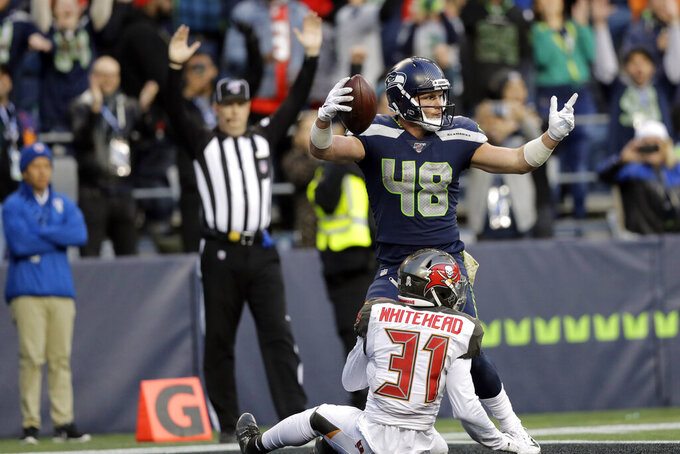Seattle Seahawks tight end Jacob Hollister (48) gets up above Tampa Bay Buccaneers free safety Jordan Whitehead after scoring a touchdown in overtime of an NFL football game, Sunday, Nov. 3, 2019, in Seattle. (AP Photo/John Froschauer)