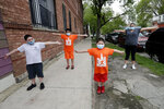 Mariana Ochoa, right, stretches with her children, Victor, 7, left, Mariano, 9, center, and Jesus, 5, in front of their home in Chicago, Friday, May 22, 2020. Chicago Run's at-home fitness programs have become an essential part of the family's routine during the coronavirus pandemic. (AP Photo/Nam Y. Huh)