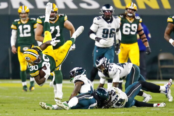 Green Bay Packers' Jamaal Williams is tripped up during the second half of an NFL football game against the Philadelphia Eagles Sunday, Dec. 6, 2020, in Green Bay, Wis. (AP Photo/Matt Ludtke)