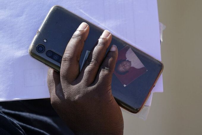 A portrait is seen in a phone case as a migrant arrives at a humanitarian center after they were released from United States Border Patrol upon crossing the Rio Grande and turning themselves in seeking asylum, Wednesday, Sept. 22, 2021, in Del Rio, Texas. (AP Photo/Julio Cortez)