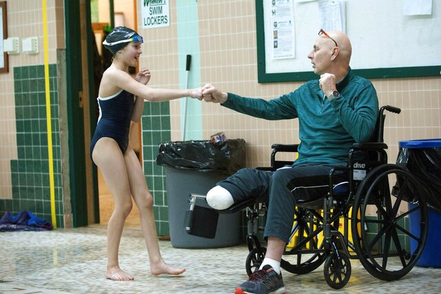 In this Jan. 7, 2020, photo, Husson University swimming coach Butch Babin fist-bumps with a student while coaching during a practice at Webber Pool in Bangor, Maine. After multiple medical procedures and amputation of part of his right leg, Babin, 57, returned to coaching on a part-time basis in October and then resumed as the head coach full time after Thanksgiving. (Natalie Williams/The Bangor Daily News via AP)