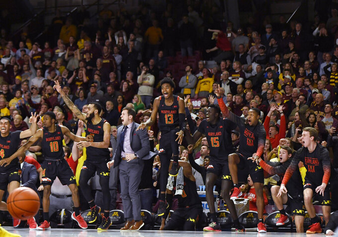 Maryland players on the bench celebrate the go-ahead 3-pointer by Darryl Morsell, not seen, against Minnesota during the second half of an NCAA college basketball game Wednesday, Feb. 26, 2020, in Minneapolis. Maryland won 74-73. (AP Photo/Hannah Foslien)