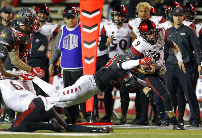 San Diego State quarterback Ryan Agnew (9) is slowed by New Mexico linebacker Sitiveni Tamaivena (26) during the first half of an NCAA college football game in Albuquerque, N.M., Saturday, Nov. 3, 2018. (AP Photo/Andres Leighton)