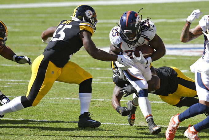 Denver Broncos running back Melvin Gordon (25) is tackled by Pittsburgh Steelers outside linebacker Bud Dupree, rear, and Devin Bush (55) during the second half of an NFL football game in Pittsburgh, Sunday, Sept. 20, 2020. (AP Photo/Don Wright)
