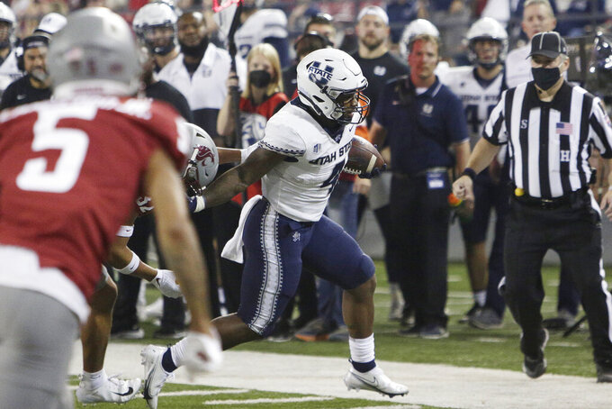 Utah State running back Calvin Tyler Jr., right, carries the ball while pressured by Washington State defensive back Tanner Moku, obscured, during the first half of an NCAA college football game Saturday, Sept. 4, 2021, in Pullman, Wash. (AP Photo/Young Kwak)