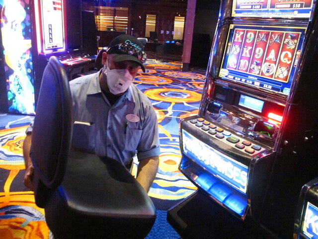 This June 3, 2020 photo shows a worker at the Ocean Casino Resort in Atlantic City N.J. removing the chair from a slot machine, part of distancing measures to help prevent the spread of the coronavirus. On June 22, New Jersey Gov. Phil Murphy announced that Atlantic City's nine casinos may reopen on July 2 at 25% of capacity. (AP Photo/Wayne Parry)