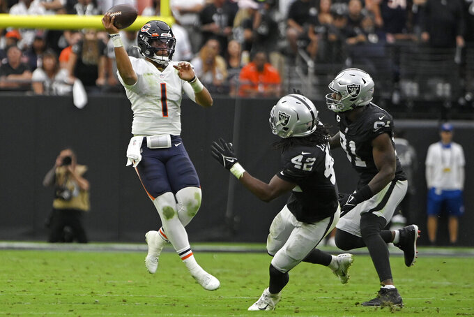 Chicago Bears quarterback Justin Fields (1) throws against the Las Vegas Raiders during the first half of an NFL football game, Sunday, Oct. 10, 2021, in Las Vegas. (AP Photo/David Becker)
