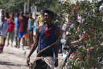 A man carries a tree branch, a Haitian symbol of protest, as demonstrators march toward the United States embassy in Port-au-Prince, Haiti, Thursday, Oct. 17, 2019. Several hundred marched to the embassy to demand that the U.S. stay out of Haiti's politics. (AP Photo/Rebecca Blackwell)