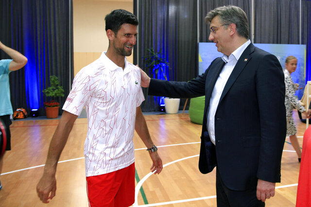 In this photo taken on Saturday June 20, 2020 and provided by the Croatian Tennis Association, Croatian Prime Minister Andrej Plenkovic, right, greets Serbian tennis player Novak Djokovic at a tournament in Zadar, Croatia. Top-ranked tennis player Novak Djokovic announced Tuesday, June 23 he and his wife have COVID-19 after he played in a series of exhibition matches he organized in Serbia and Croatia with zero social distancing amid the coronavirus pandemic. (AP Photo/Mario Cuzic, Croatian Tennis Association via AP)