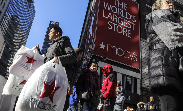 FILE - In this Nov. 29, 2019, file photo a shopper leaves a Macy's department store with bags in both hands during Black Friday shopping in New York. Macy's swung to a loss and saw its sales drop 22% during its fiscal third quarter as the department store chain continues to struggle to attract shoppers in a pandemic. (AP Photo/Bebeto Matthews, File)