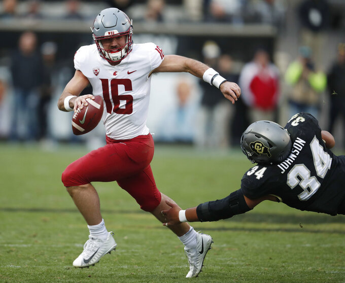 Washington State quarterback Gardner Minshew, left, scrambles away from Colorado defensive lineman Mustafa Johnson in the second half of an NCAA college football game Saturday, Nov. 10, 2018, in Boulder, Colo. Washington State won 31-7. (AP Photo/David Zalubowski)