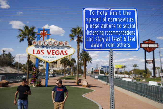 """FILE - In this March 21, 2020, file photo, a sign advises people to practice social distancing to slow the spread of the coronavirus at the """"Welcome to Fabulous Las Vegas Nevada"""" sign amid a shutdown of casinos along the Las Vegas Strip in Las Vegas. Economic signs are pointing up for Nevada gambling and tourism heading into the Memorial Day holiday weekend. New reports on Thursday, May 27, 2021, showed that casinos won $1 billion in April, the second month in a row, and monthly visitor volume increased for a fourth straight month. (AP Photo/John Locher, File)"""