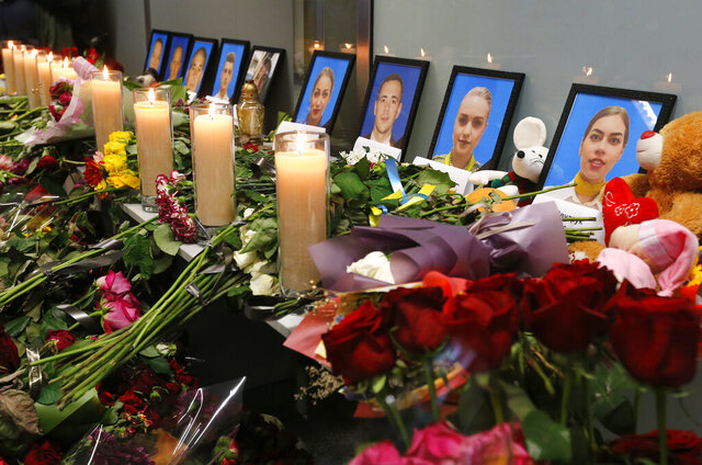 Flowers and candles are placed in front of portraits of the flight crew members of the Ukrainian 737-800 plane that crashed on the outskirts of Tehran, at a memorial inside Borispil international airport outside Kyiv, Ukraine, Saturday, Jan. 11, 2020. Ukraine's President Volodymyr Zelenskiy says that Iran must take further steps following its admission that one of its missiles shot down Ukrainian civilian airliner. He also expressed hope for the continuation of the crash investigation without delay. A team of Ukrainian investigators is in Iran. (AP Photo/Efrem Lukatsky)