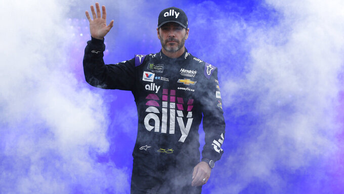 Jimmie Johnson waves to fans during driver introductions prior to the start of the NASCAR Cup series auto race at Richmond Raceway in Richmond, Va., Saturday, April 13, 2019. (AP Photo/Steve Helber)