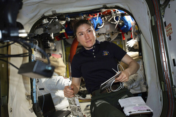 In this April 8, 2019 photo made available by NASA, astronaut and Expedition 59 Flight Engineer Christina Koch works on U.S. spacesuits inside the Quest airlock of the International Space Station. Koch will remain on board until February 2020, approaching but not quite breaking Scott Kelly's 340-day U.S. record. (NASA via AP)