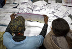 Electoral workers count ballots in view of party agents after the close of polls at the Parkhurst Primary School in Johannesburg, South Africa Wednesday, May 8, 2019. South Africans are voting Wednesday in a national election that pits President Cyril Ramaphosa's ruling African National Congress against top opposition parties Democratic Alliance and Economic Freedom Fighters, 25 years after the end of apartheid. (AP Photo/Ben Curtis)