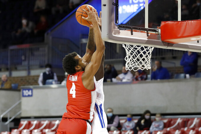 Houston forward Justin Gorham (4) attempts a dunk over the defense of SMU forward Yor Anei, background, during the first half of an NCAA college basketball game in Dallas, Sunday, Jan. 3, 2021. (AP Photo/Roger Steinman)