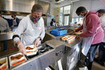 Volunteers Sheeran Howard, left, and Ibrahim Bahrr, right, package meals at Community Servings, which prepares and delivers scratch-made, medically tailored meals to individuals & families living with critical & chronic illnesses, Tuesday, Jan. 12, 2021, in the Jamaica Plain neighborhood of Boston. Food is a growing focus for insurers as they look to improve the health of the people they cover and cut costs. Insurers first started covering Community Servings meals about five years ago, and CEO David Waters says they now cover close to 40%. (AP Photo/Charles Krupa)