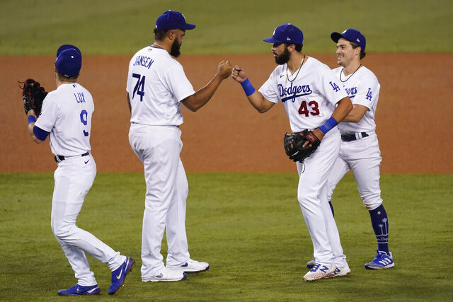 Los Angeles Dodgers' Gavin Lux, Kenley Jansen, Edwin Rios and Enrique Hernandez, from left, celebrate a 9-5 win over the Los Angeles Angels in a baseball game Friday, Sept. 25, 2020, in Los Angeles. (AP Photo/Ashley Landis)