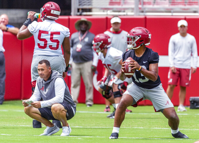 Alabama quarterback Tua Tagovailoa (13) works through drills as offensive Coordinator Steve Sarkisian, crouching, watches in Alabama's fall camp fan-day college football scrimmage, Saturday, Aug. 3, 2019, at Bryant-Denny Stadium in Tuscaloosa, Ala. (AP Photo/Vasha Hunt)