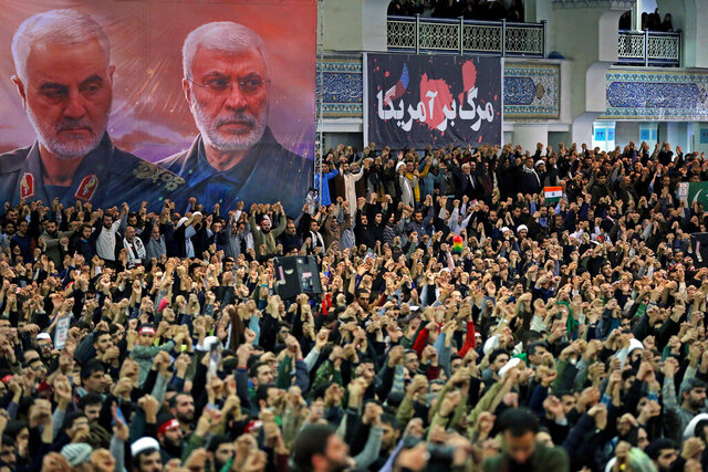 In this picture released by the official website of the office of the Iranian supreme leader, worshippers chant slogans during Friday prayers ceremony, as a banner show Iranian Revolutionary Guard Gen. Qassem Soleimani, left, and Iraqi Shiite senior militia commander Abu Mahdi al-Muhandis, who were killed in Iraq in a U.S. drone attack on Jan. 3, and a banner which reads in Persian: