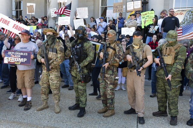 """FILE - In this May 2, 2020, file photo, people, including those with the boogaloo movement, demonstrate against business closures due to concern about COVID-19, at the State House in Concord, N.H. Facebook says it is banning a """"U.S.-based anti-government network"""