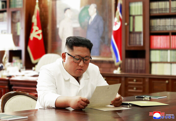 In this undated file photo provided on Sunday, June 23, 2019, by the North Korean government, North Korean leader Kim Jong Un reads a letter from U.S. President Donald Trump. South Korea's President Moon Jae-in on Tuesday, June 25, 2019, said North Korean and U.S. officials are holding