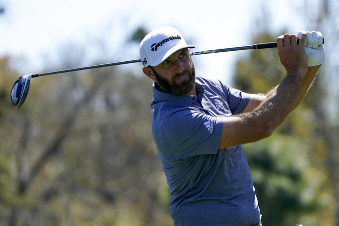 Dustin Johnson watches his tee shot on the ninth hole during the second round of the The Players Championship golf tournament Friday, March 12, 2021, in Ponte Vedra Beach, Fla. (AP Photo/John Raoux)