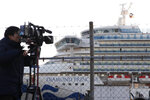 A TV cameraman films the quarantined ship Diamond Princess, background, anchored at Yokohama port in Yokohama, near Tokyo, Tuesday, Feb. 18, 2020. The cruise ship will begin letting passengers off the boat on Wednesday after it's been in quarantined for 14 days. (AP Photo/Koji Sasahara)