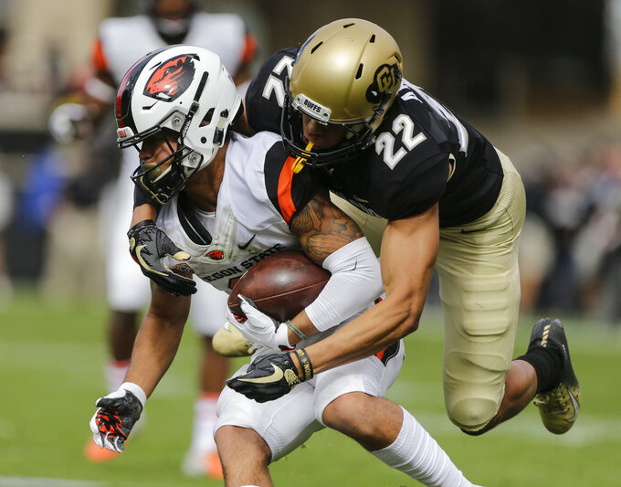 Colorado's Daniel Arias (22) tackles Oregon State punt-returner Trevon Bradford (8) during the first half of an NCAA college football game, Saturday, Oct. 27, 2018, in Boulder, Colo. (AP Photo/Jack Dempsey)