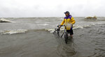 Frank Arena pushes his bike through the water as winds from Tropical Storm Barry push water from Lake Pontchartrain over the seawall Saturday, July 13, 2019, in Mandeville, La. (AP Photo/David J. Phillip)