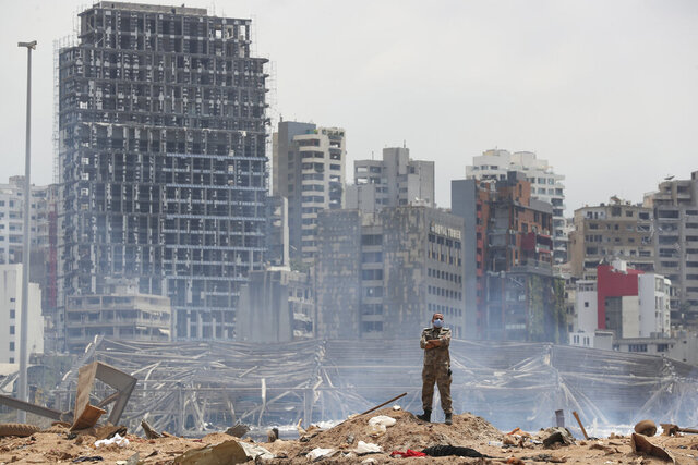 FILE - In this Aug. 6, 2020, file photo, a soldier stands at the devastated site of the explosion in the port of Beirut, Lebanon. Lebanon's president is calling for the international community's support to rebuild the country's main port and destroyed neighborhoods after last month's catastrophic explosion that decimated the facility. President Michel Aoun spoke Wednesday, Sept. 23, 2020, in a prerecorded speech to the U.N. General Assembly, telling world leaders that Lebanon is facing multiple crises that pose an unprecedented threat to the small country's existence. (AP Photo/Thibault Camus, Pool)