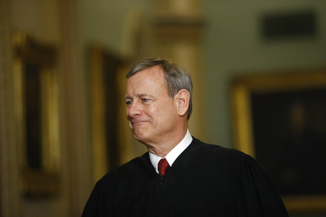 "FILE - In this Jan. 16, 2020, file photo Chief Justice of the United States, John Roberts walks to the Senate chamber at the Capitol in Washington. Roberts told graduating seniors at his son's high school that the coronavirus has ""pierced our illusion of certainty and control"