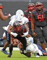 Miami quarterback D'Eriq King (1) is tackled by North Carolina linebacker Chazz Surratt (21) during the first half of an during an NCAA college football game at Hard Rock Stadium In Miami Gardens, Fla, Saturday, Dec, 12, 2020. (Al Diaz/Miami Herald via AP)