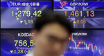 A currency trader walks by the screens showing the foreign exchange rates at the foreign exchange dealing room in Seoul, South Korea, Thursday, April 25, 2019. Asian shares were mixed Thursday after U.S. stocks closed lower, giving back some of its gains a day after the S&P 500 and Nasdaq hit record highs. (AP Photo/Lee Jin-man)