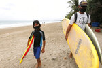Tourists wearing face masks carry their surfboard at Kuta beach, Bali, Indonesia on Thursday, July 9, 2020. Indonesia's resort island of Bali reopened after a three-month virus lockdown Thursday, allowing local people and stranded foreign tourists to resume public activities before foreign arrivals resume in September.(AP Photo/Firdia Lisnawati)