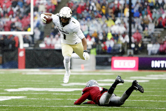Colorado running back Jaren Mangham, left, jumps over Washington State cornerback Marcus Strong during the first half of an NCAA college football game in Pullman, Wash., Saturday, Oct. 19, 2019. (AP Photo/Young Kwak)