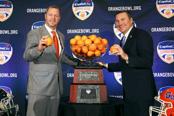 Virginia Cavaliers head coach Bronco Mendenhall, left, and Florida Gators head coach Dan Mullen, right, pose for a photograph during a news conference for the Orange Bowl NCAA college football game, Sunday, Dec. 29, 2019, in Fort Lauderdale, Fla. Florida plays Virginia in the Orange Bowl on Dec. 30. (AP Photo/Mario Houben)