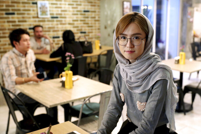 """In this Monday, Oct. 7, 2019 photo, 21-year-old Afghan refugee Fatemeh Jafari poses for a photo at her basement Tehran coffee shop, in downtown Tehran, Iran. More than 3 million Afghans including as many as 2 million who entered without legal permission, live in the Islamic Republic, according to United Nations estimates. Jafari hopes her Telma, or """"Dream,"""" Café in Tehran will help bridge the divides and xenophobia Afghans can face in Iran. (AP Photo/Ebrahim Noroozi)"""