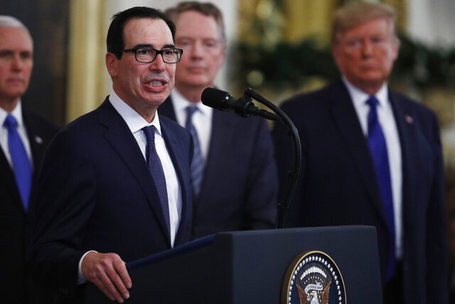 Secretary of Treasury, Steven Mnuchin, at podium, speaks as U.S. Trade Representative Robert Lighthizer, back second from right and President Donald Trump, right, listen during a signing ceremony for