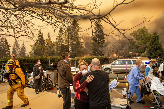 FILE - This Nov. 8, 2018, file photo shows Nurse Cassie Lerossignol hugs as coworker as the Feather River Hospital burns while the Camp Fire rages through Paradise, Calif. The scale of disaster in the Camp Fire was unprecedented, but the scene of people fleeing wildfire was familiar, repeated numerous times over the past three years up and down California from Redding and Paradise to Santa Rosa, Ventura and Malibu. In many of those communities, motorists became stuck in traffic as officials tried to evacuate thousands onto a few roads leading away from the flames. (AP Photo/Noah Berger, File)
