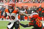 Cincinnati Bengals running back Joe Mixon (28) rushes against Cleveland Browns cornerback Denzel Ward (21) during the second half of an NFL football game, Sunday, Dec. 8, 2019, in Cleveland. (AP Photo/Ron Schwane)