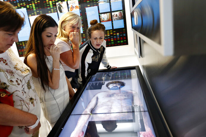 In this April 12, 2018, photo, people look at an interactive exhibit at the Crime Lab Experience in the Mob Museum in Las Vegas. For years the museum has showcased the area's storied past in organized crime, but visitors can now also enjoy a speakeasy, a use of deadly force training experience, and an interactive crime lab exhibit. (AP Photo/John Locher)