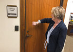 In this May 10, 2019 photo, Sergeant at Arms Leta Edwards of the Oregon Senate knocks on the office door of Republican Sen. Fred Girod in order to bring him to the Senate floor and reach a quorum in Salem, Ore. Girod was not in. Republican senators began their walkout on Tuesday, May 7, 2019, to protest an education-funding bill that imposes a tax on some businesses. (AP Photo/Andrew Selsky)