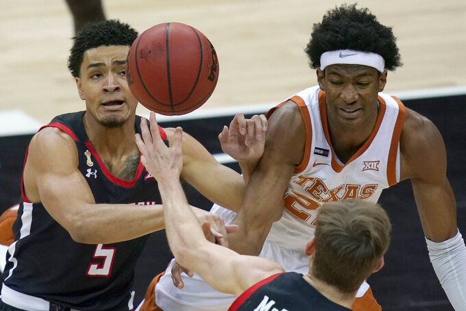 Texas Tech Red guard Micah Peavy (5) and Texas forward Kai Jones (22) chase a loose ball during the first half of an NCAA college basketball game in the quarterfinal round of the Big 12 men's tournament in Kansas City, Mo., Thursday, March 11, 2021. (AP Photo/Orlin Wagner)