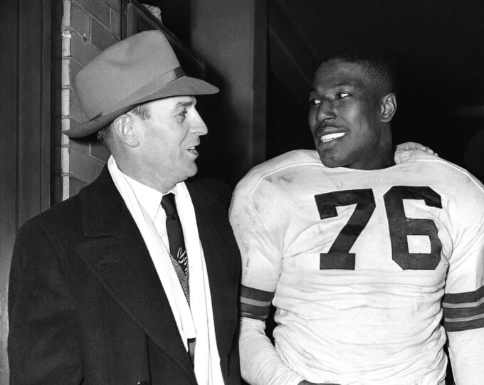 FILE - In this Dec. 19, 1948, file photo, Cleveland Browns fullback Marion Motley, right, stands with coach Paul Brown after a football game against Buffalo in Cleveland. Brown never saw color, and in 1946 he recruited Motley and Bill Willis for his Cleveland team in the All-America Football Conference. (AP Photo/Harold Valentine, File)